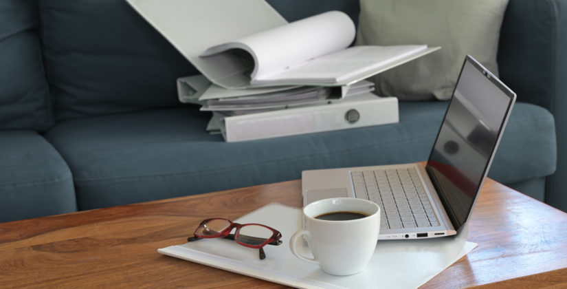 Laptop Unterlagen im Wohnzimmer - bildlich für Homeoffice